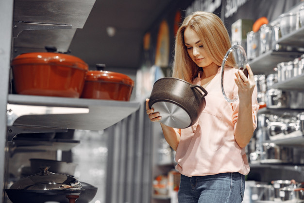 image of woman inspecting-buying cookware and kitchen utensils