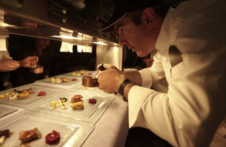 image of experienced chef garnishing food in a restaurant